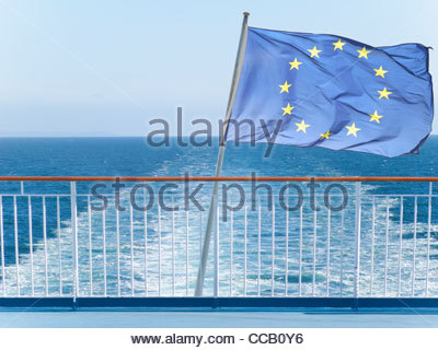 European Union flag on railing of ship with ocean water in background - Stock Photo