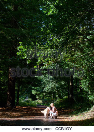 Woman squatting on path in park with dog - Stock Photo