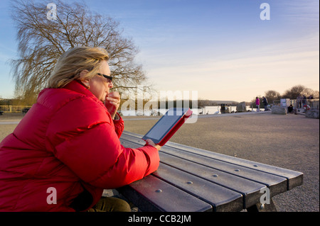 Woman using an Ipad 2 computer tablet outdoors - Stock Photo