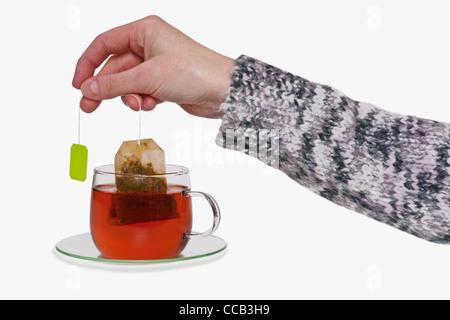 aus einer Tasse mit Tee wird der Teebeutel herausgezogen   the tea bag is pulled out of a cup with tea - Stock Photo