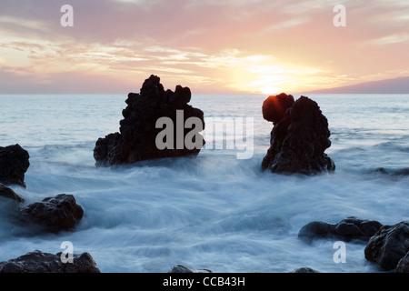 Sea swirling around rocks at sunset in Playa San Juan, Tenerife, Canary Islands, Spain - Stock Photo