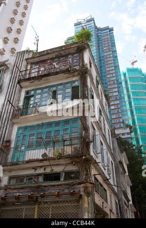 old 4 storey housing building in between apartment skyscrapers hong kong hksar china asia - Stock Photo