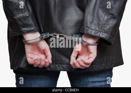 einem Menschen sind die Hände auf dem Rücken durch Handschellen gefesselt | a man's hands are tied up by handcuffs - Stock Photo