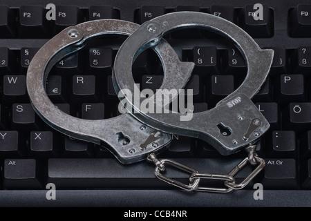 Handschellen liegen auf einer Computertastatur   handcuffs are on a computer keyboard - Stock Photo