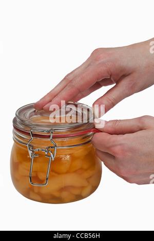 Ein Glas mit eingeweckten Birnenstückchen wird geöffnet | a jar with home canned pieces of pears will be opening - Stock Photo