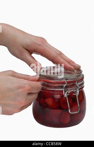 Ein Glas mit eingeweckten Erdbeeren wird geöffnet | a jar with home canned strawberries will be opening - Stock Photo