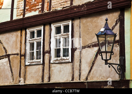 Old wooden windows on a dilapidated half-timbered house in the UNESCO German town of Quedlinburg in Saxony Anhalt, - Stock Photo