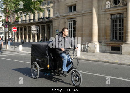 French delivery man on a tricycle riding down a Paris street. - Stock Photo