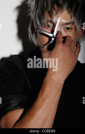 young man holding scissors up to his eye - Stock Photo