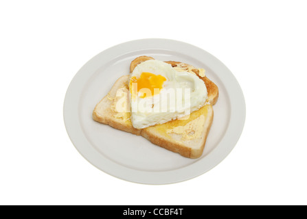 Heart shaped fried egg on buttered toast on a plate isolated against white - Stock Photo