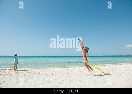 Boy flying kite on beach, girl jumping to catch - Stock Photo