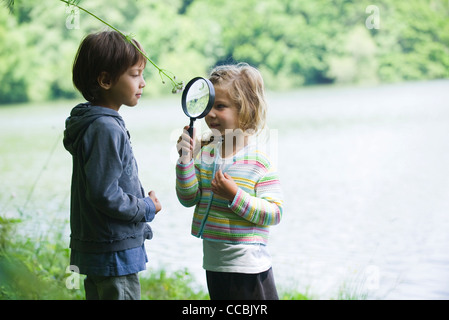 Children playing with magnifying glass outdoors - Stock Photo