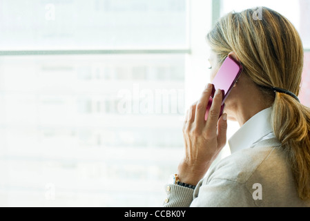 Woman using cell phone, looking out window - Stock Photo