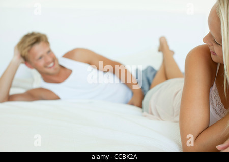 Couple lying on bed, woman smiling over her shoulder at man - Stock Photo