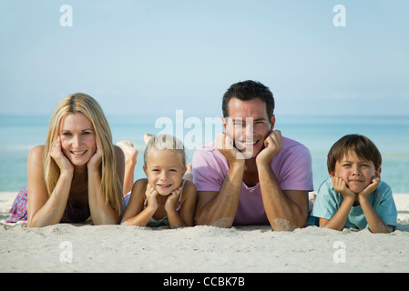 Family lying on sand at the beach, portrait - Stock Photo