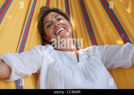 Woman relaxing in hammock, portrait - Stock Photo