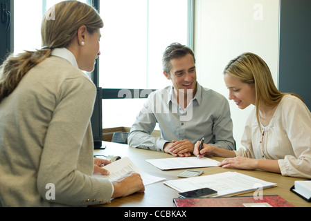 Couple reading over contract in office - Stock Photo