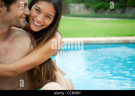 Couple embracing by swimming pool, portrait - Stock Photo
