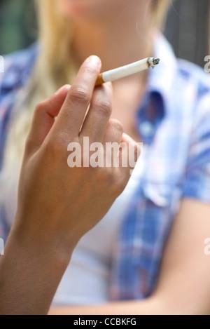 Woman's hand holding lit cigarette - Stock Photo