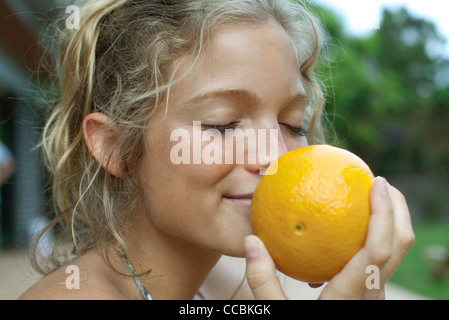 Woman smelling fresh orange - Stock Photo