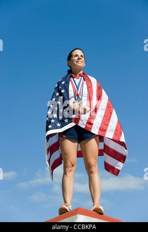 Female athlete being honored on podium, wrapped in American flag - Stock Photo
