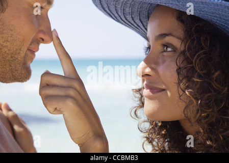Couple at the beach, woman touching man's nose - Stock Photo