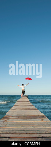 Man jumping on pier with umbrella, rear view - Stock Photo