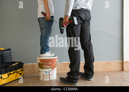 Father and son doing home improvement, low section - Stock Photo