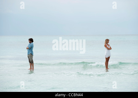 Couple standing apart in sea with backs turned toward each other - Stock Photo