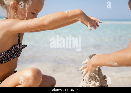 Girl playing in sand at the beach - Stock Photo
