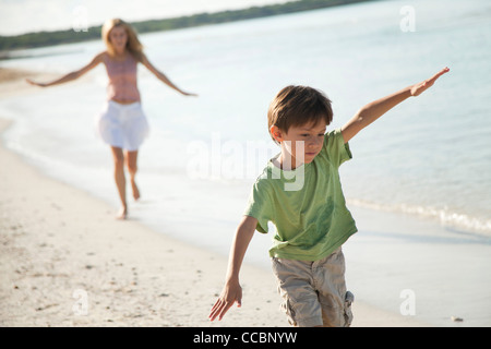 Boy running with arms out at the beach - Stock Photo