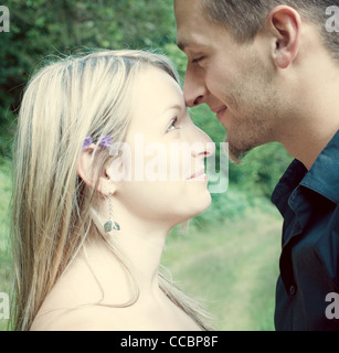 Couple nuzzling outdoors - Stock Photo