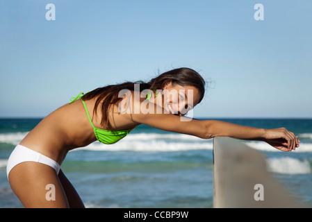 Woman in bikini stretching at the beach, portrait - Stock Photo