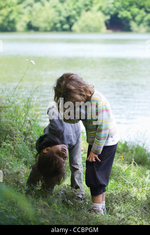Children playing with magnifying glass outdoors