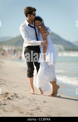 Bride and groom embracing at the beach - Stock Photo