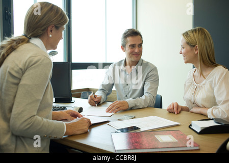 Couple talking with financial advisor - Stock Photo