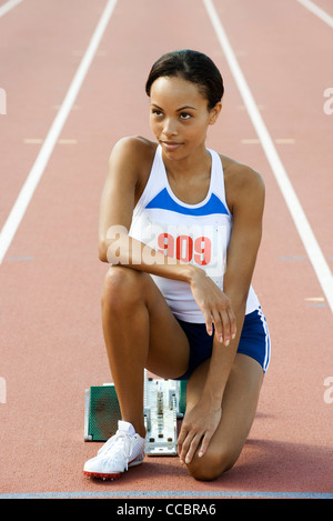 Female runner crouched at starting line - Stock Photo