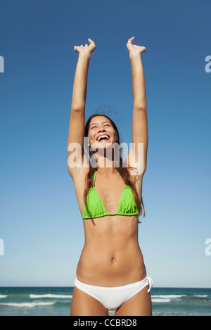 Woman in bikini stretching at the beach - Stock Photo