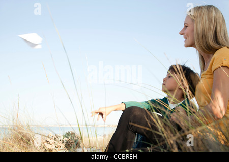 Boy sitting with his mother, throwing paper airplane - Stock Photo