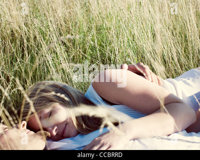 Couple napping together in tall grass - Stock Photo
