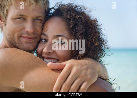 Couple embracing at the beach, portrait - Stock Photo