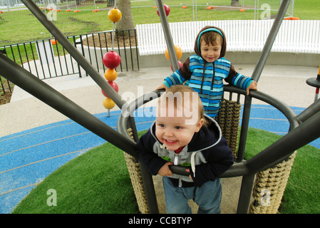 Toddler boys playing on playground - Stock Photo