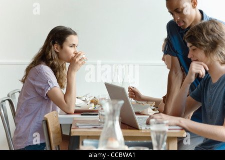 Friends in restaurant, woman dining, man using laptop computer - Stock Photo