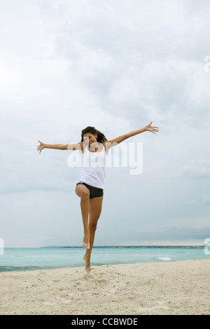 Young woman jumping in air on beach - Stock Photo