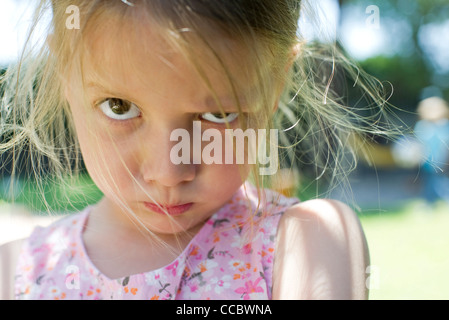 Little girl staring at camera with lips pursed - Stock Photo