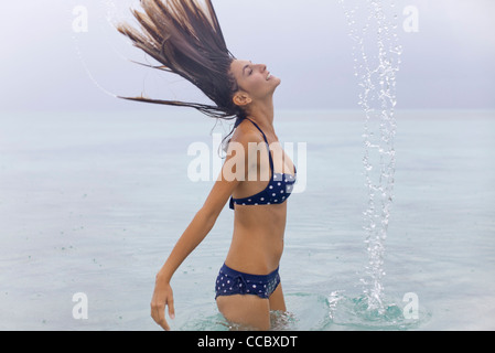 Woman tossing wet hair in water - Stock Photo