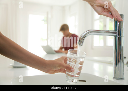Woman filling glass of water at kitchen sink, cropped - Stock Photo
