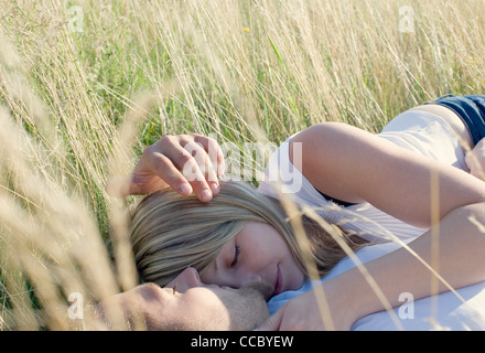 Couple lying together in field of tall grass - Stock Photo