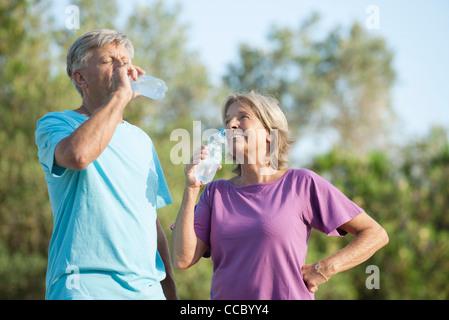 Senior couple drinking bottled water outdoors - Stock Photo