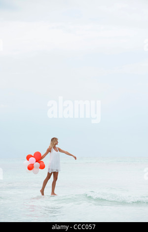 Woman walking on water, carrying bunch of balloons - Stock Photo